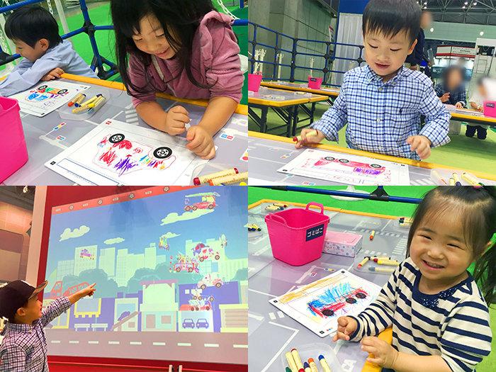 おえかきトミカタウンの実施風景。クレヨンを使って思い思いのトミカを描く子供たち、動くぬりえを指差す子供など。