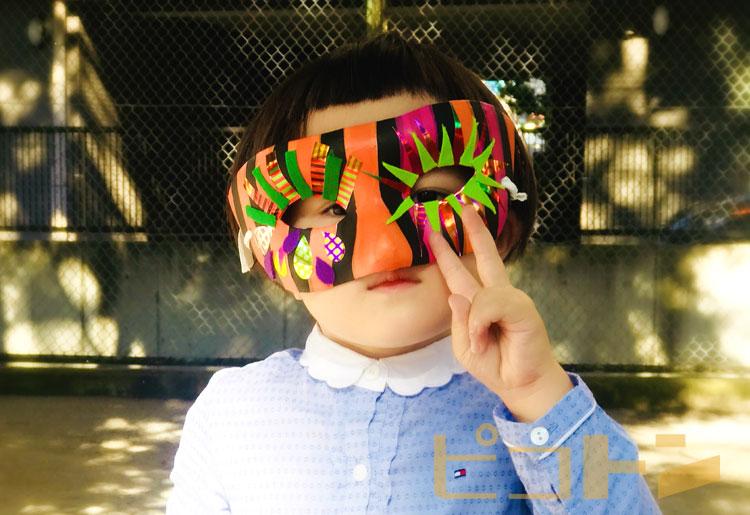 ハロウィンマスクを着けてピースサインを出す子供