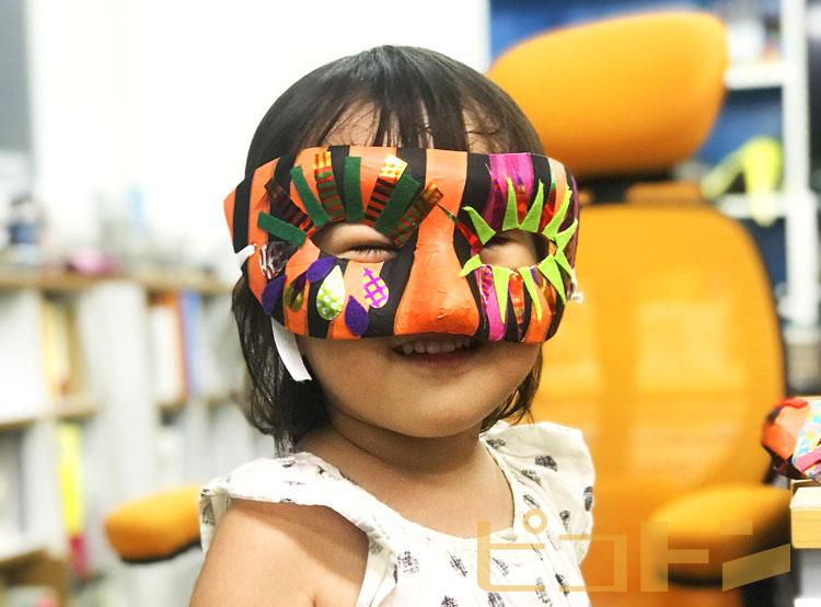 ハロウィンマスクを着けて笑顔の子供