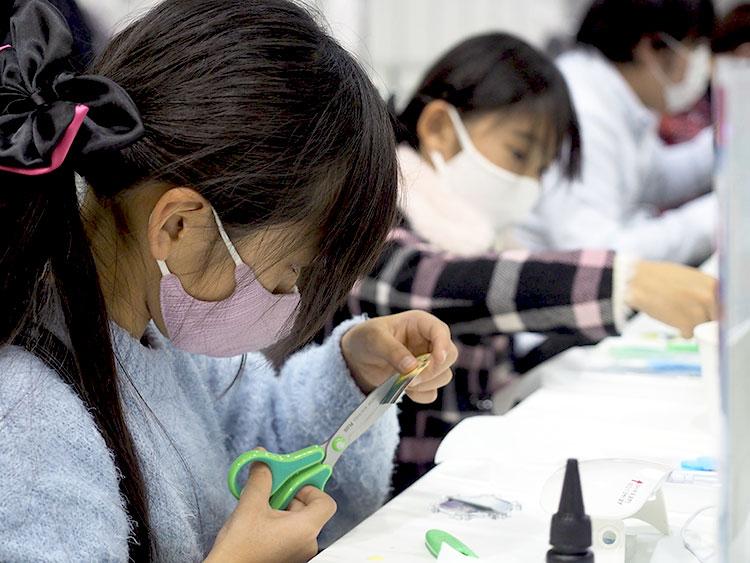 デザインシールを切っている子供の手。