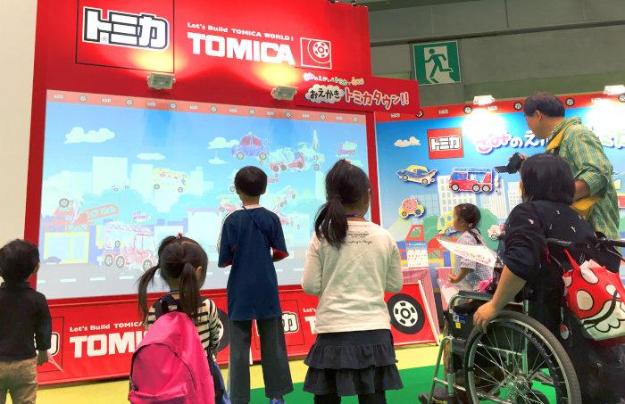 描いたトミカが動く!おえかきトミカタウンイベント風景。巨大なスクリーンの前に集まる子供たち