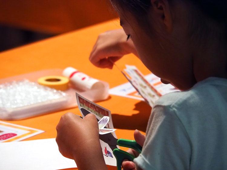 アートタイルに貼る熱転写シールを切る子供