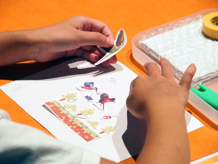 台紙に熱転写シールを配置する子供の手